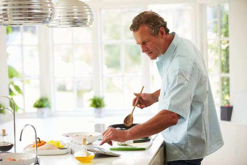 Middle Aged Man Following Recipe On Digital Tablet
